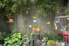 Decoratievlinder die in tuin met muurachtergrond vliegen stock foto