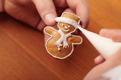 Decoratin cookie. Close up of hands decorating Christmas cookie stock photo