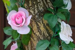 Decorating of artificial flowers with a tree trunk. stock photography