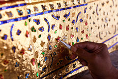 Decorating the base of the image of Buddha with stained glass. Hand of artist decorating the base of the image of Buddha with stained glass Stock Photos
