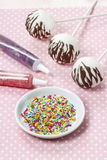 Decorating cake pops with colorful sprinkles Royalty Free Stock Photos