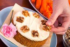 Decorating carrot cake with walnuts Stock Photography