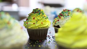 Decorating of chocolate cupcakes with cream, Close up of hand sprinkling topping onto fresh cupcakes stock video footage