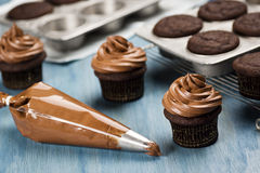 Decorating Chocolate Cupcakes with Frosting. Chocolate cupcakes are being decorated with frosting from a pastry bag after cooling royalty free stock photos