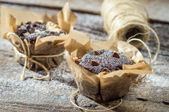 Decorating chocolate muffins with nuts. On old wooden table Royalty Free Stock Image