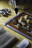 Decorating choux ceam with chocolate sauce. Decorating choux ceam with chocolate sauce on wiid table with baking tray,measuring cup,measuring spoon and whisk Stock Photography