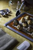 Decorating choux ceam with chocolate sauce. Decorating choux cream with chocolate sauce on wood table with baking tray,measuring cup,measuring spoon and whisk Stock Photo