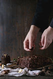 Decorating of christmas chocolate yule log. Decorating process of homemade Christmas chocolate yule log by woman's hands with chocolate chips over old wooden Royalty Free Stock Photography