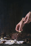Decorating of christmas chocolate yule log. Decorating process of homemade Christmas chocolate yule log by woman's hands with chocolate stars over old wooden Royalty Free Stock Photo