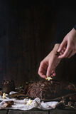 Decorating of christmas chocolate yule log. Decorating process of homemade Christmas chocolate yule log by woman's hands with chocolate stars over old wooden Stock Photography
