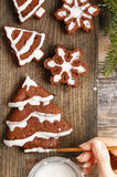 Decorating christmas gingerbread chocolate cookies with white ic. Ing. Festive dessert Royalty Free Stock Image
