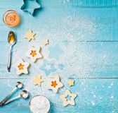 Baking Christmas Cookies. Decorating Christmas Linzer cookies with icing sugar and apricot jam on a blue wooden background stock photos