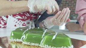 Decorating the Christmas treats. Cake in the shape of Christmas tree. stock footage