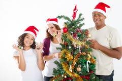 Decorating Christmas tree. Happy family of three decorating Christmas tree together Stock Photo