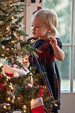 Decorating the Christmas Tree. Little Girl Hanging Ornaments on a Christmas Tree Royalty Free Stock Image