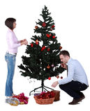 Decorating the Christmas tree. Studio shot of a young couple decorating the Christmas tree against a white background Royalty Free Stock Images
