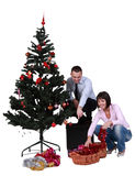 Decorating the Christmas tree. Studio shot of a young happy couple decorating the Christmas tree, against a white background Stock Photo