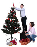 Decorating the Christmas tree. Studio shot of a young couple decorating the Christmas tree, against a white background Stock Image