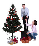Decorating the Christmas tree. Studio shot of a young couple having fun while decorating the Cristmas tree Royalty Free Stock Photography