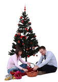 Decorating the Christmas Tree. Studio shot of a young happy couple decorating the Christmas Tree, against a white background Royalty Free Stock Photos
