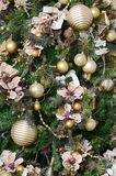 Decorating Christmas tree close up. Decoration bulb, green fir tree, golden x-mas toys and lights. Use for Christmas and New years. Celebration background stock image