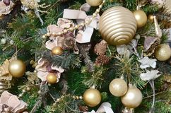 Decorating Christmas tree close up. Decoration bulb, green fir tree, golden x-mas toys and lights. Use for Christmas and New years. Celebration background stock photo