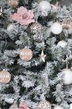 Decorating Christmas tree close up. Decoration bulb, snowy green fir tree, pink x-mas toys and lights. Use for Christmas and New. Years celebration background royalty free stock photography