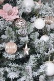 Decorating Christmas tree close up. Decoration bulb, snowy green fir tree, pink x-mas toys and lights. Use for Christmas and New. Years celebration background stock photos