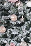 Decorating Christmas tree close up. Decoration bulb, snowy green fir tree, pink x-mas toys and lights. Use for Christmas and New. Years celebration background stock photo