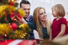 Decorating Christmas tree. Little girl with parents decorating the Christmas tree together Stock Image