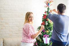 Decorating a Christmas tree with my boyfriend. Portrait of a happy young women putting some Christmas decorations on a tree with her boyfriend at home stock photo