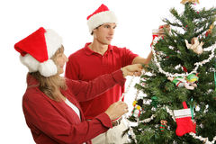 Decorating Christmas Tree Together. Middle aged mother and her young adult son decorating the Christmas tree together Stock Images