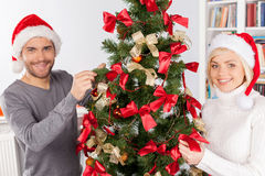 Decorating a Christmas tree together. Cheerful young couple decorating a Christmas tree together Royalty Free Stock Images