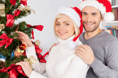 Decorating a Christmas tree together. Cheerful young couple decorating a Christmas tree together Royalty Free Stock Photography