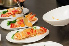 Decorating cooked lobster on plate Stock Images