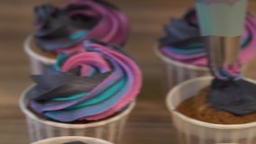 Decorating cup-cake with cream. Culinary master class design cupcakes, cream cupcakes from the pastry bag. Using cooking. Bag, confectioner making multicolor stock footage