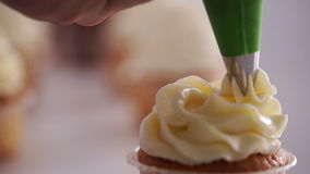 Decorating cup-cake with cream. stock video