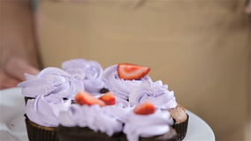 Decorating cupcakes with strawberries. Process of Baking cupcake stock video footage