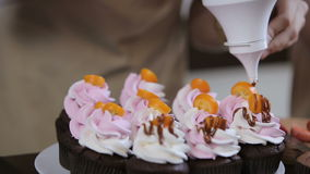 Decorating cupcakes. Two young women are making cupcakes stock video footage