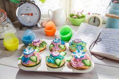 Decorating delicious cupcakes with cream and decoration Stock Photos