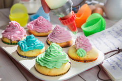 Decorating delicious muffins with cream and decoration Stock Images