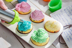Decorating delicious muffins with cream Royalty Free Stock Image