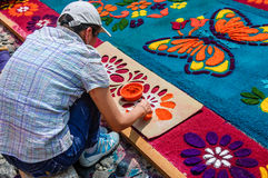 Decorating dyed sawdust flowers on Lent carpet, Antigua, Guatemala. Antigua, Guatemala - March 22, 2015: Local decorates carpet with floral pattern of dyed stock photo