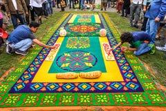 Decorating dyed sawdust Lent carpets, Antigua, Guatemala. Antigua, Guatemala - March 13, 2016: Locals watch men decorate handmade dyed sawdust Lent carpets for stock photography