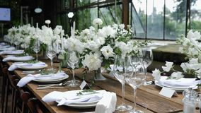 Decorating a Festive table. Wedding Table Decoration with Bouquets of Natural Fresh Flowers for a Family Feast