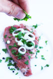 Decorating fresh beef with greens Royalty Free Stock Photography
