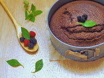 Decorating freshly baked chocolate cake with berries and mint leaves. Selective focus Stock Photography
