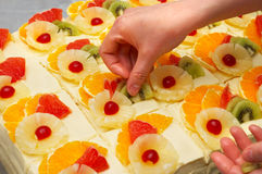 Decorating the fruit cakes. Decorating the custard filled cakes with fruits Stock Images