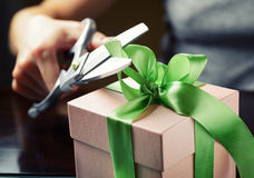 Decorating gift box with green ribbon using scissor Royalty Free Stock Image