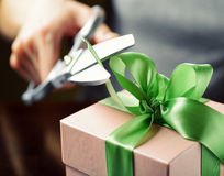 Decorating gift box with green ribbon using scissor Royalty Free Stock Photo